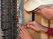An electrician tightening connection in a breaker box