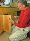 Carpenter installs door-pull on the base of an entertainment center