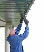 stock photo of christmas lights  - Man installing Christmas lights - JPG