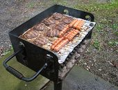 stock photo of hot dog  - Hamburgers and hot dogs on a charcoal grill - JPG