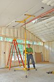 Man using lift to position drywall panel for installation on ceiling