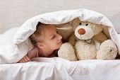 Adorable Little Child Girl Playing With Teddy Bear In Bed In Morning. Baby With A Teddy Bear Under T poster