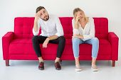 Couple In Love Girlfriend And Boyfriend Having Quarrel On Red Sofa At Home, Indoors . Upset poster