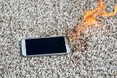 Mobile phone explodes and burns. Cell Phone explosion and fire on a beige carpet. Smart Phone Danger poster