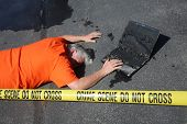 Crime Scene. A man lays dead on the sidewalk with a burned computer behind CRIME SCENE DO NOT CROSS  poster
