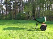 stock photo of spreader  - Broadcast spreader on green grass after fertilizing the lawn - JPG