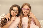 Girls Children Posing With Grimaces Photo Booth Props. Pajamas Party Concept. Girls Friends Having F poster