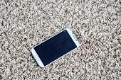 generic cell phone. cell phone on a carpet. blank screen with room for text or images.   poster
