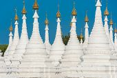 Kuthodaw Pagoda contains the worlds biggest book. There are 729 white stupas with caves with a marbl poster