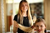 Young Hairdresser Holding Hair Of Female Client. Smiling Hairstylist Picking Haircut For Girl. Two B poster