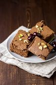 Three Pieces Of Tasty Homemade Chocolate Brownies On White Plate Decorated With Cherry And Pistachio poster