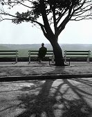 picture of bereavement  - a solitary man watches the setting sun from a city park 