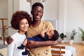 Portrait Of Loving Parents Holding Newborn Baby At Home In Loft Apartment poster