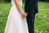 Hands Of Bride And Groom. New Young Couple Holding Hands After Their Wedding. Young Married Couple H poster