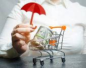 Business Woman Provides Protection For A Supermarket Trolley With Money. Guarantee Of Protection Of  poster