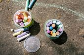 Plastic Bucket With Chalk For Drawing On Asphalt. Multi-colored Crayons For Childrens Drawings. Draw poster