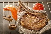 Meat Steak Baked In Foil And Baked Vegetables On A Metal Grill. Close-up poster