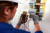 image of  multimeter  - Female electrician checking a fusebox - JPG