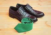 Green Rolled Necktie And Fashionable Black Mens Shoes. Selective Focus On Necktie. poster