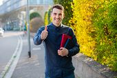 University. Smiling Young Student Man Holding Thumb Up And Books On A University Background. Confide poster