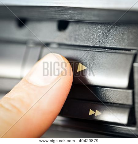 Finger pushing play button on a vintage audio cassette deck