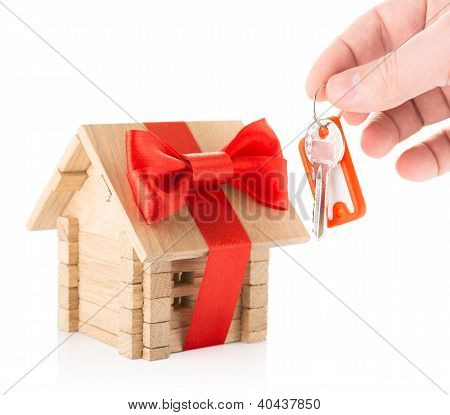 Hand with keys and wooden house