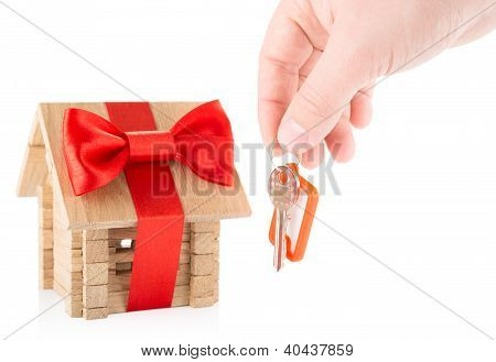wooden house and hand with keys