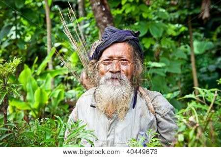 BLITAR, JAVA, INDONESIA - JANUARY 9: Old Kolufo man with bow and arrows on the natural green forest background. January 9, 2012 in small village near Blitar, Java,Kolufo still hunt with bow and arrow.