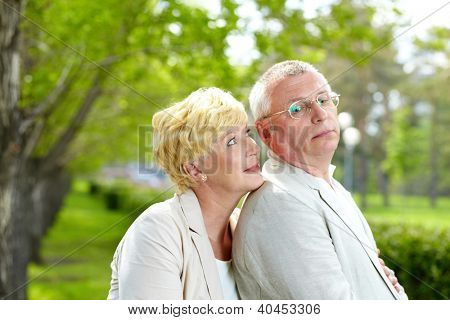 Mature woman and her husband flirting outside