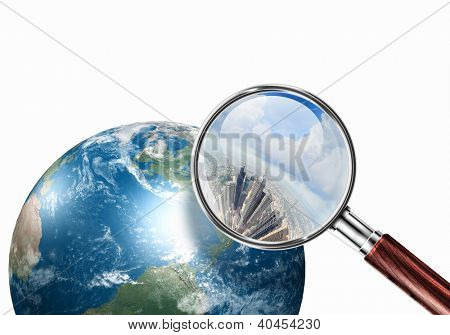 Conceptual mini planet with skyscrapers on it under a magnifying glass. Elements of this image are furnished by NASA