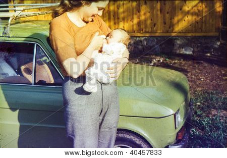 Vintage photo of mother breastfeeding her daughter (1981)