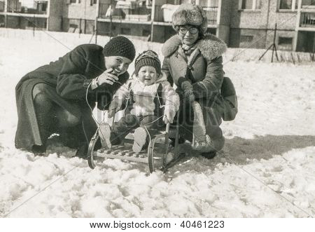 Vintage photo of mother, aunt and little girl on sled (early eighties)