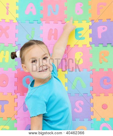 Cute little girl is pointing at letter B
