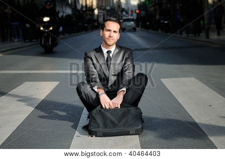 Young Handsome Businessman Sitting In A Crosswalk
