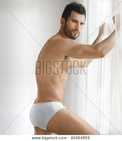 Very sexy young male muscular model in white underwear in front of window