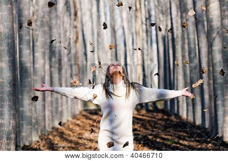 Beautiful Blonde Girl With Falling Leaves In The Autumn Park