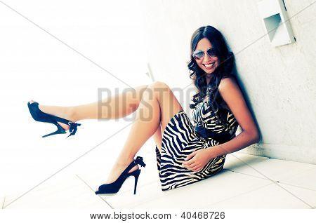 Engraçado modelo feminino na moda com saltos altos, sentados no chão