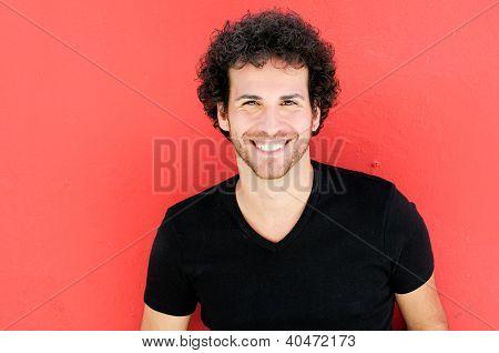 Homem com penteado encaracolado sorrindo no contexto urbano