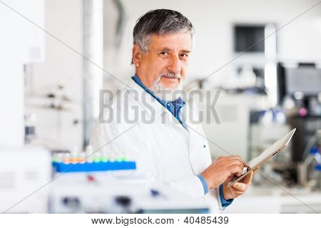 Senior doctor using his tablet computer at work (color toned image)