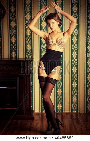 Charming young woman in seductive lingerie posing over vintage background.