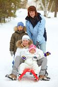 stock photo of toboggan  - Happy kids and their parents tobogganing in park - JPG