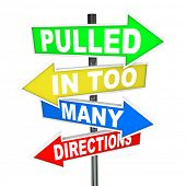 image of directional  - The words Pulled in Too Many Directions on signs symbolizing feelings of stress - JPG
