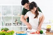 stock photo of flirty  - Flirty couple chopping vegetables for a weekend lunch - JPG