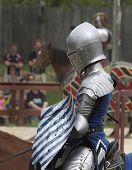 image of jousting  - A proud Knight patiently waits on his horse for his turn to joust at a reenactment  - JPG