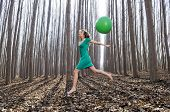 stock photo of vaquero  - Beautiful blonde girl dressed in green jumping into the woods with a balloon in Fuente Vaqueros Granada Spain - JPG