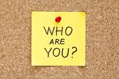 foto of personality  - Who Are You written on an yellow sticky note pinned on a cork bulletin board - JPG