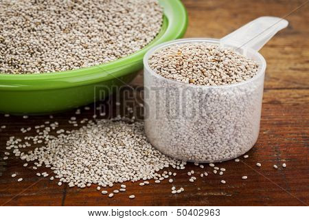 white chia seeds -measuring scoop and small side dish bowl against grunge wooden surface