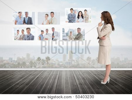 Businesswoman staring at futuristic interface showing partners