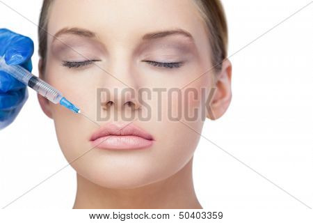 Relaxed beautiful model on white background having botox injection above the lips