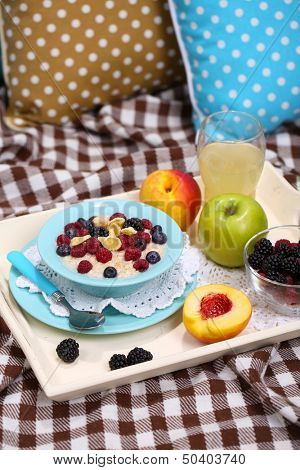 Oatmeal in plate with berries on napkins on wooden tray on bad